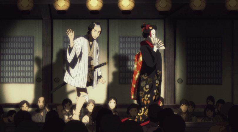 Kikuhiko and Shin walk out under spotlights onto a stage, surrounded by an audience. Kikuhiko is dressed in a kimono, Shin in more casual masculine robes.