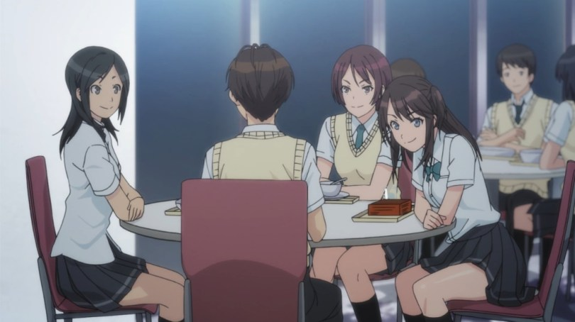 Shoichi sits at a round school lunch table with his back to us, the three girls around the table leaning in and looking at him with smiles on their faces.