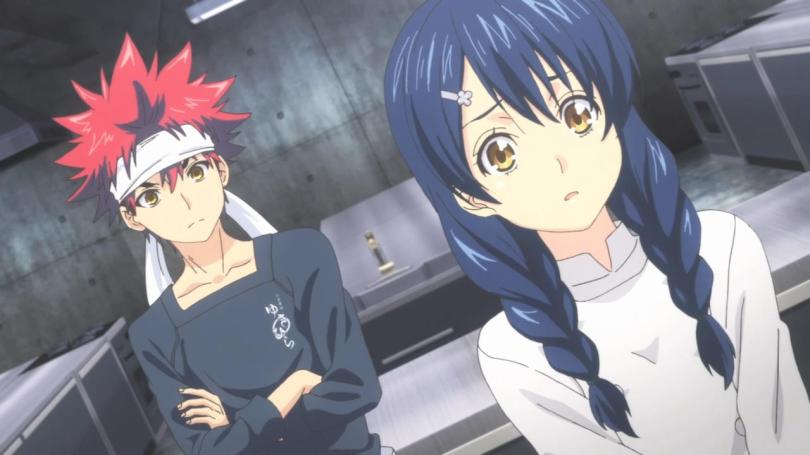Soma stands in the background of a kitchen with his arms folded, watching Megumi as she looks worried.