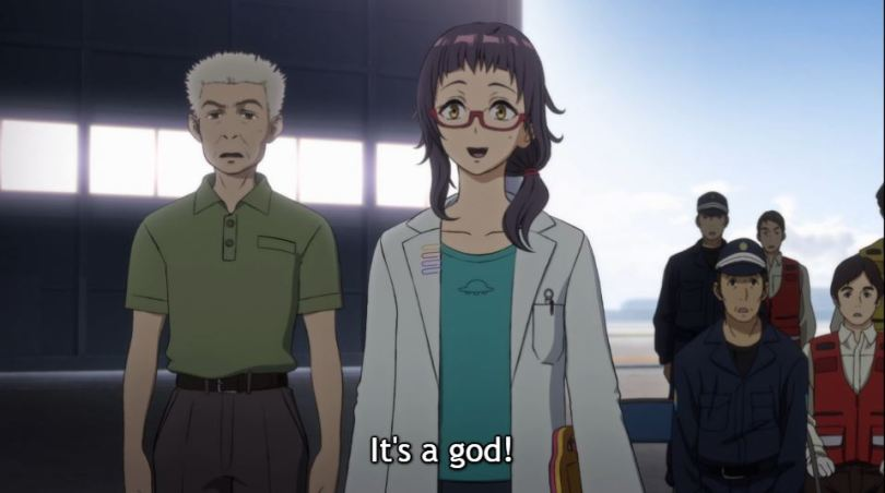 "A young female scientist with glasses and a ponytail smiles as an older male scientist and military officers stand behind her looking worried. Subtitle: ""It's a god!"""