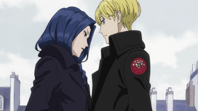 A long-haired woman in a black coat stands in profile as if walking past a short-haired man in a matching jacket. She appears to be saying something quietly to him while he glances at her out of the corner of his eye, mildly surprised.