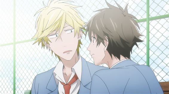 A brunette boy in a school uniform peers intently at a blonde boy, who side-eyes him