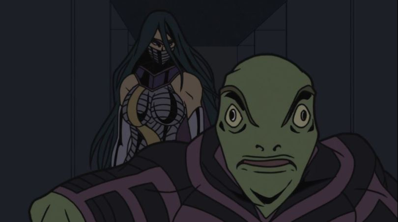 A woman in a metal outfit and lower-face mask stands behind a frog-faced man