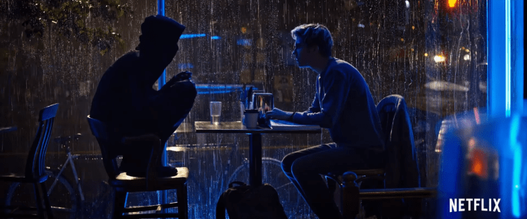 Two people cast in shadow sit at a cafe table in front of a window. The person on the left is wearing a hoodie and all in black, perched atop his chair, knees to chest. The person on the right is a blonde young man with his arms on the table, leaning forward slightly. Outside the window it is dark and rainy.