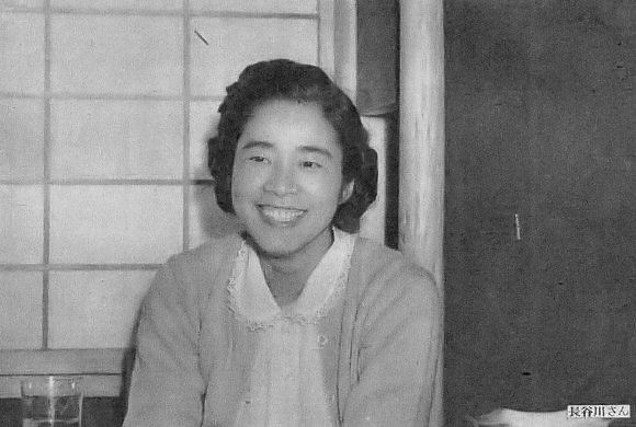 A black-and-white photo of a young Japanese woman in a cardigan with her hair pinned up