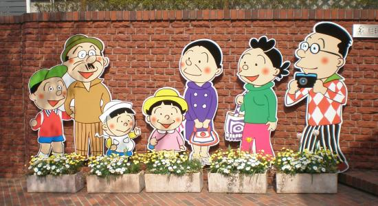 A photo of a sequence of cartoonish cardboard cutouts standing against a brick wall. The cutouts are (left to right) a boy in a baseball cap and red polo, an older man with a short mustache, olive bowler hat, and brown shirt and slacks; a toddler in a white sailor cap and white apron; a young girl in a pink shirt and rounded yellow hat; an older woman with her hair pinned up wearing a purple coat and holding a red purse; a younger woman with messy hair wearing a green turtleneck, pink slacks, and carrying a purple handbag; and a man in glasses wearing a red-checked shirt and holding a camera