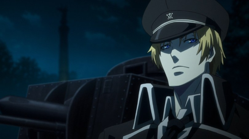 A blonde man wearing a black military brimmed hat and jacket stands in front of a tank, looking smug