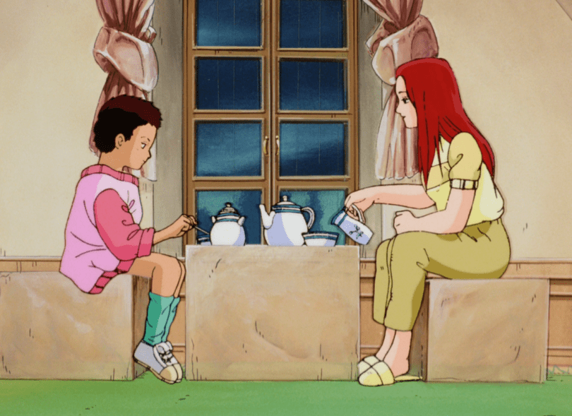 Two people sit across from each other at a table, with a window behind them. There is a tea set on the table. To the right is a woman with long hair in casual shirt and pants pouring tea. To the left is a young boy in an oversized shirt, looking down.