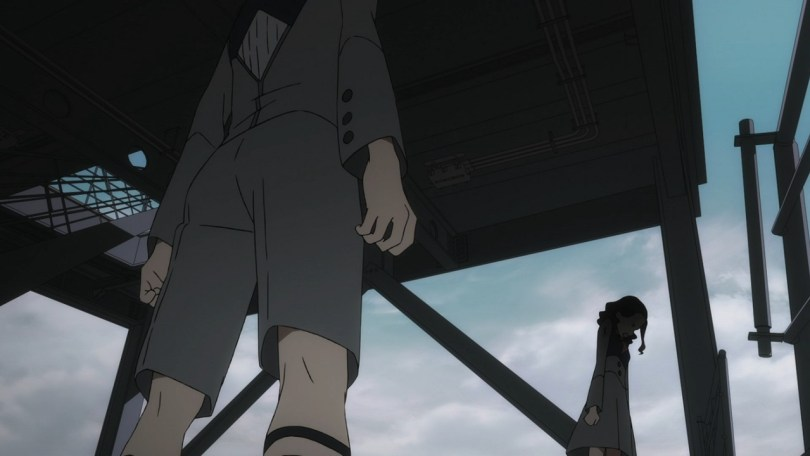A skewed camera angle: An upshot of boy in a uniform with short-pants, his face off-screen, facing a girl in a similar uniform. She is in shadow and seen in profile. Behind them are girders, a platform, and open sky, as if they are in some kind of loading dock.