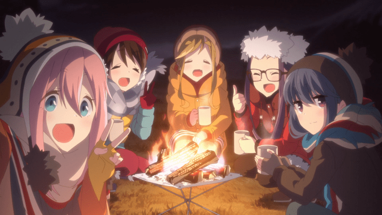 A group of five teenage girls wearing winter coats and hats, huddled around a campfire, look towards the camera and smile.