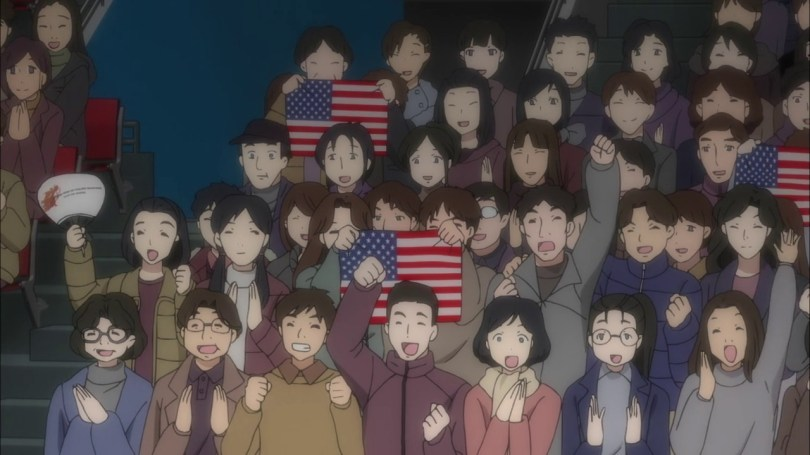 A crowd of people sitting in stands in some sort of arena, all cheering, many holding US flags.