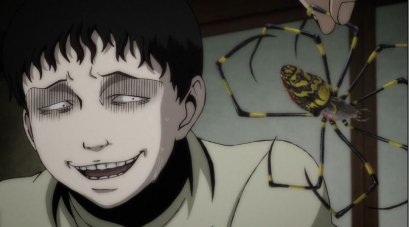 pale Souichi with a frozen, uncomfortable expression staring at a dead spider being held in front of his face