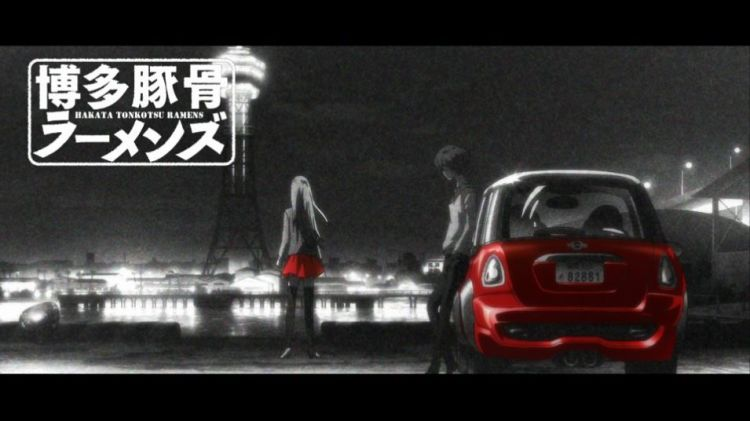 """A black-and-white image of a person in feminine clothing leaning on a railing and looking out over a cityscape while a masculine figure leans against a car. On-screen text says """"Hakata Tonkotsu Ramens."""""""