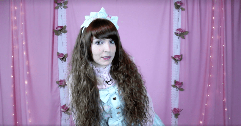 Vlogger Tyler Willis in Lolita clothing in front of a pink backdrop, taken from one of her videos