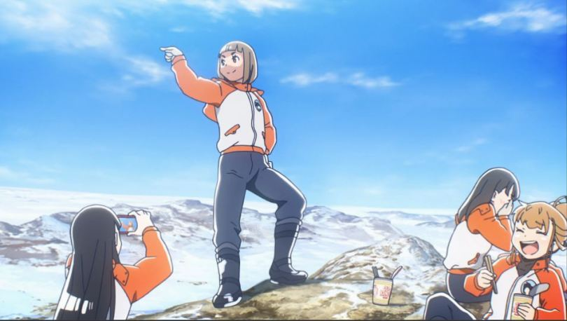 Four girls in matching coats and pants stand in front of an arctic landscape. One is striking a pose atop a small hill, one is taking a photo, and the other two are laughing.