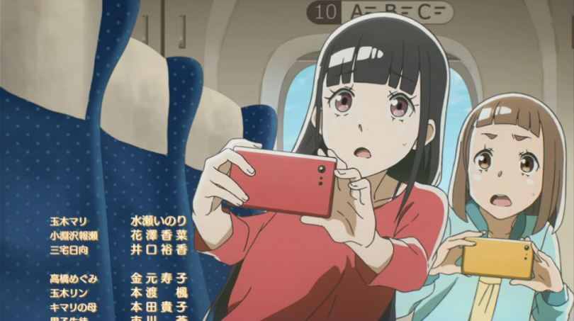 Mari and Shirase leaning forward in their train seats, trying to get a picture of something offscreen with their phones