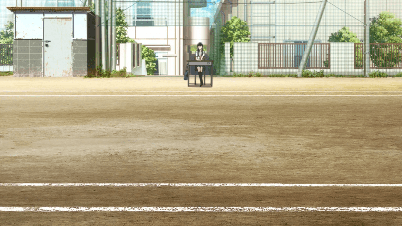 A long shot of Akira sitting at a desk in front of a track field.