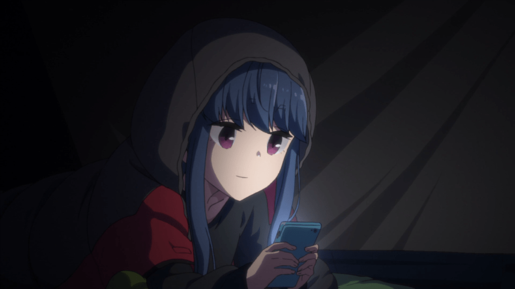 A teen girl in winter clothes sits in a darkened tent, looking at her glowing phone screen.