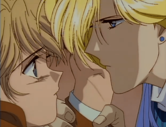 A blonde man (Nakago) holds Yui's wrist and brings his face close to hers. He looks serious; she looks startled.