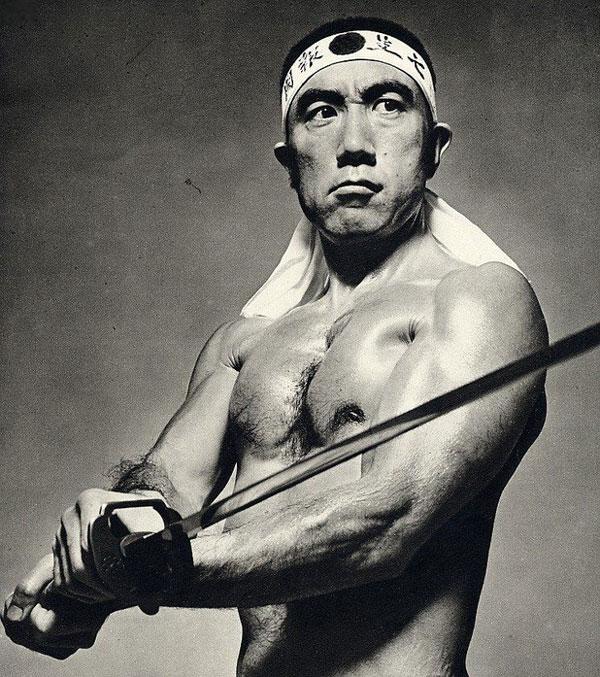 Mishima shirtless and holding a samurai sword