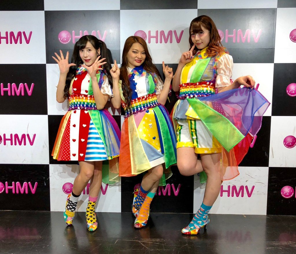 Three Japanese women in rainbow-colored outfits pose in front of a checkboard wall.