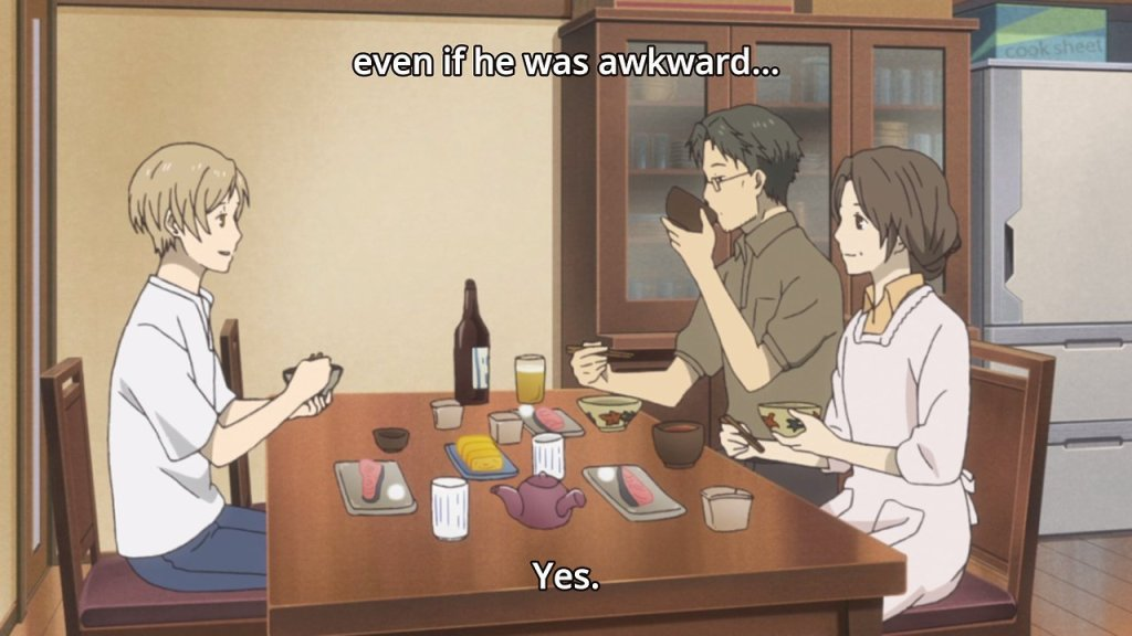 "Natsume and his two guardians sit at a kitchen table with a meal in front of them, looking happy. Subtitles read ""even if he was awkward."""