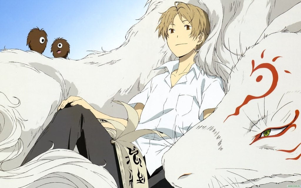 Natsume sits pillowed against Nyanko-sensei in his larger, wolf-life yokai form. Two soot sprite-like creatures are behind him.