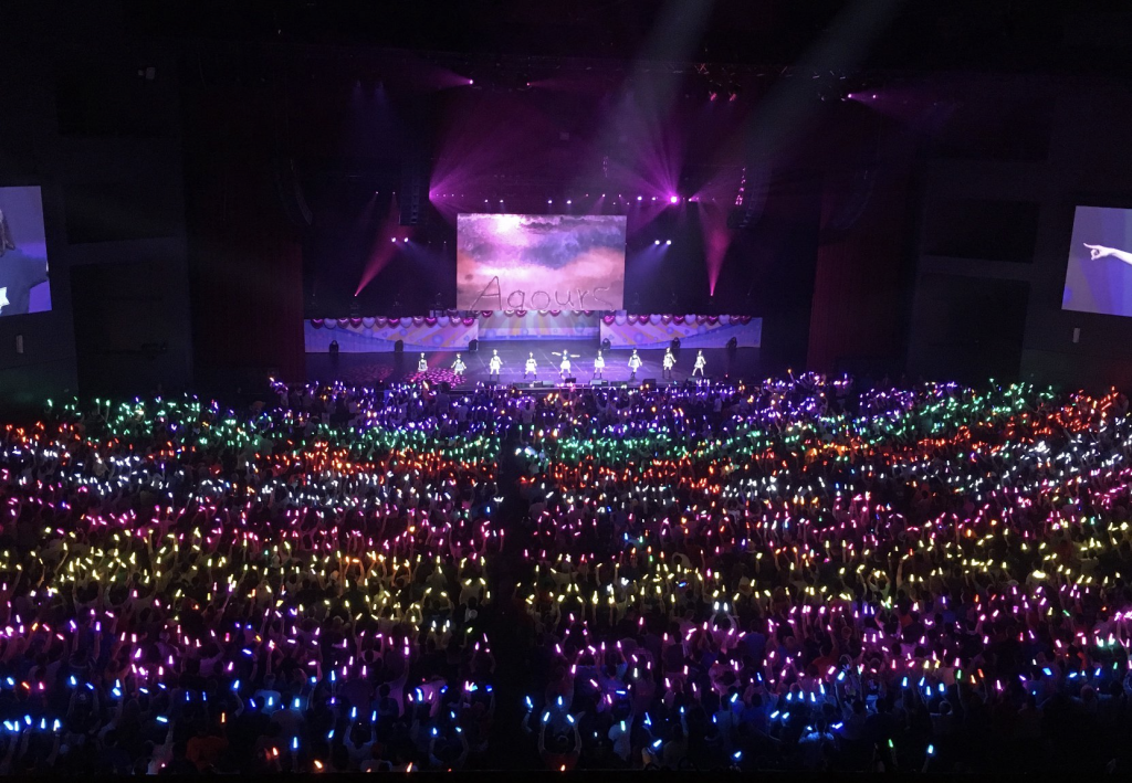 A photo of a stage in the middle of a concert. It's lit in pinks. The audience is holding multi-colored glowsticks.