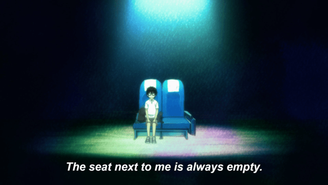 """A boy sits in a theatre chair next to one other, empty theatre chair. He is under a spotlight and surrounded by darkness. Subtitles read: """"The seat next to me is always empty."""""""