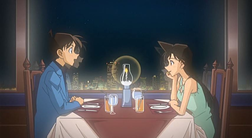 Ran and Shinichi sit across from each other by candle light with the Tokyo skyline behind them
