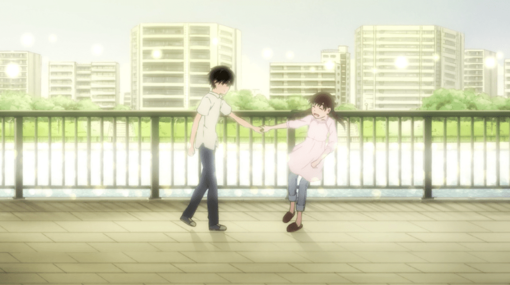 A teen boy and teen girl hold hands as the girl falls away from him, laughing. The background is a fence and river softly lit with sunshine.