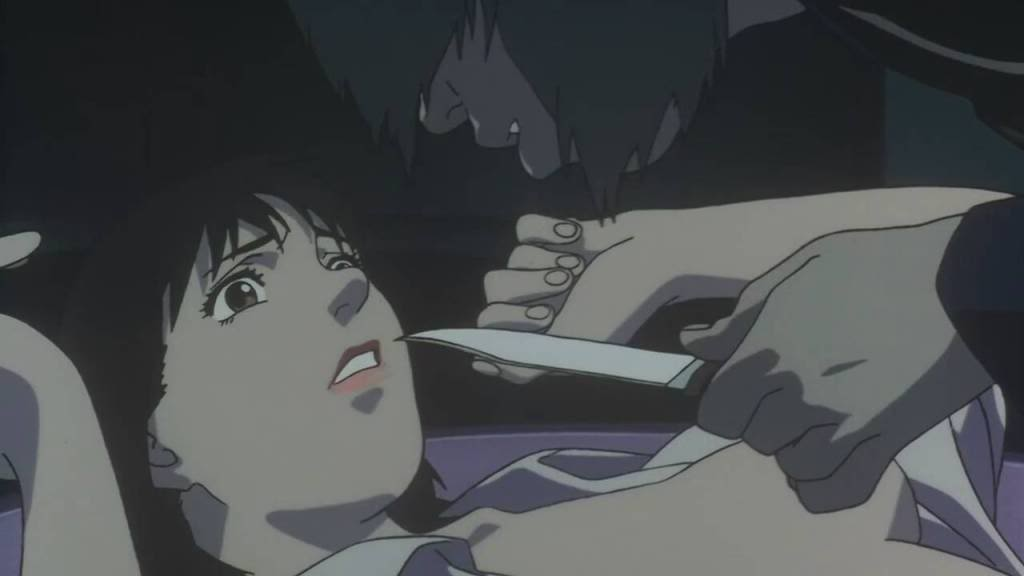 Mima being threatened by her stalker with a knife, her shirt torn open
