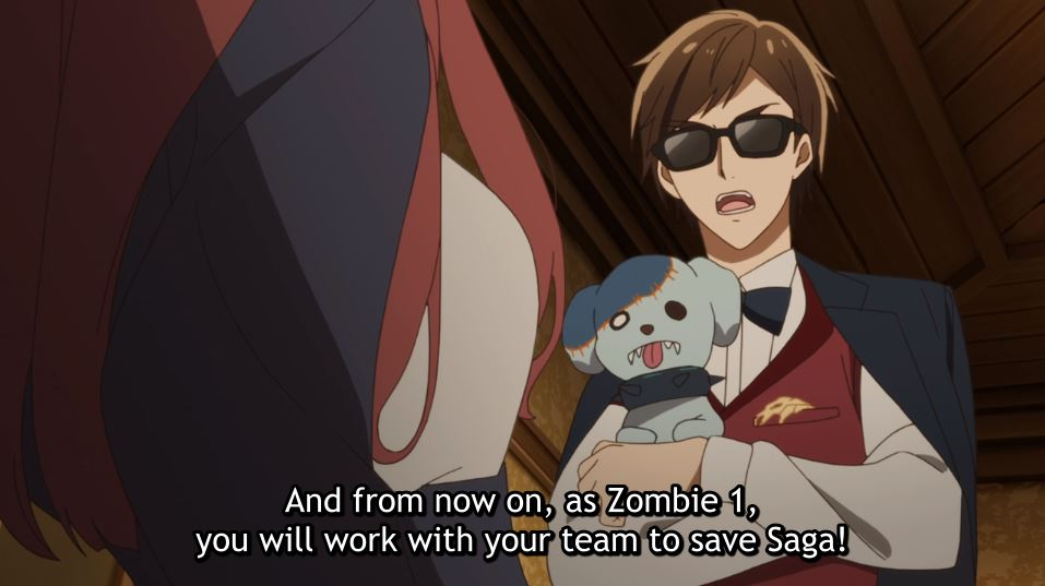 Kotaru holding a zombie dog, talking to Sakura. subtitle: And from now on, as Zombie 1, you will work with your teammates to save Saga