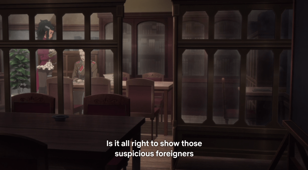 "A shot of a study seen through multiple glass-paneled doors. A Hispanic woman stands next to a desk where a blonde man is sitting. Subtitles read ""Is it all right to show these suspicious foreigners"""