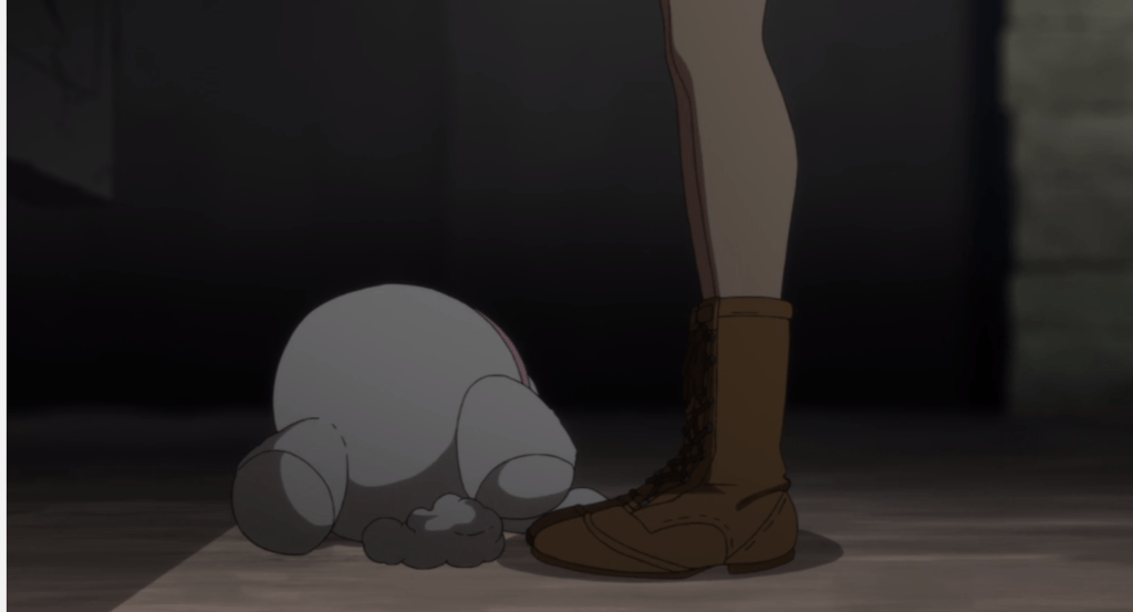 A shot from the floor that just shows a girl's feet and a plush bunny sitting beside them.