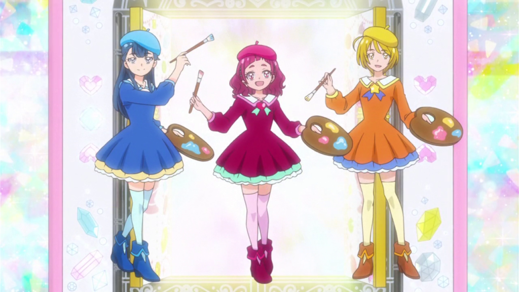 Three girls in blue, maroon and orange dresses and berets pose with paint brushes and pallates