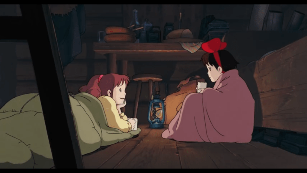 Kiki wrapped in a blanket, talking to Ursula