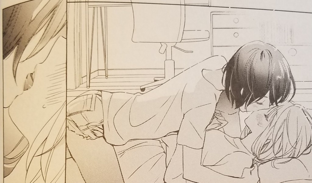 Kase leans over Yamada on a bed, kissing her
