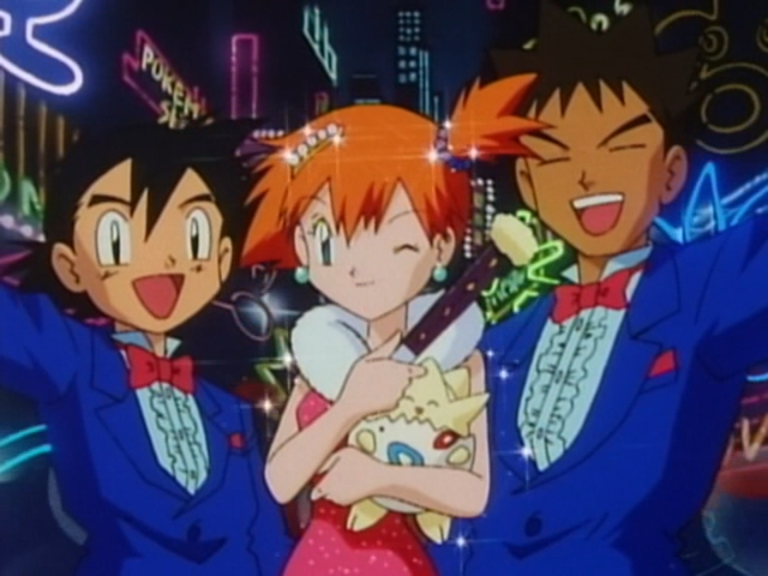 Ash, Misty, and Brock strike a pose while wearing tuxedos and a sparkly dress.