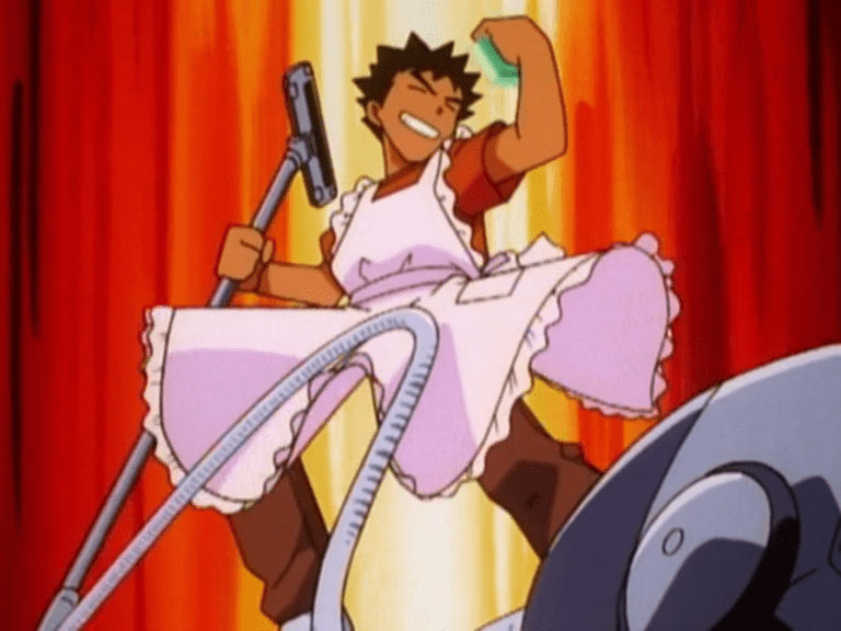Brock, wearing a frilly pink apron, holding a vaccuum nozzle in one hand and a sponge in the other, strikes a heroic pose