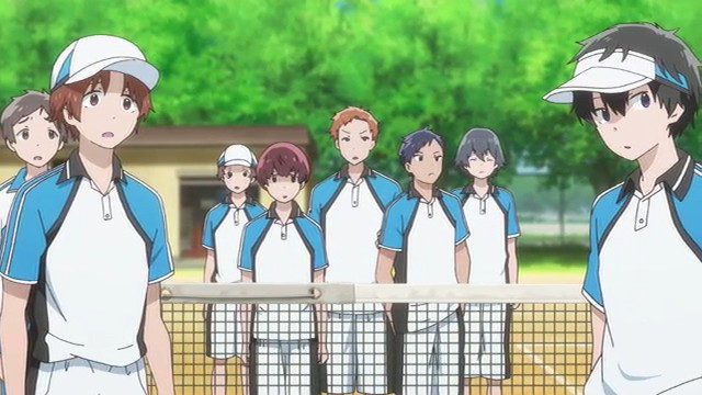 The soft tennis club on a tennis court. Most of the team is behind the net, with two players in front of it.