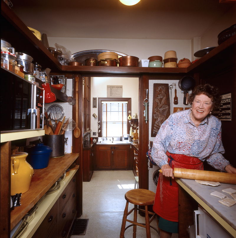 Julia Child in a cozy home kitchen, wearing an apron and holding a rolling pin
