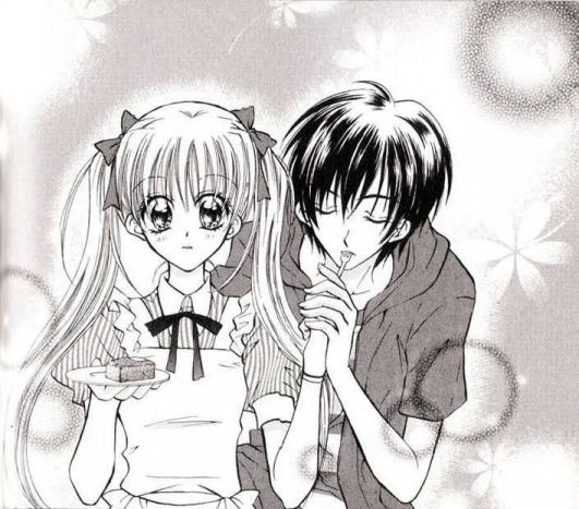 The main girl in Kitchen Princess blushes slightly as a boy holds her hand and takes a bite off a fork she's holding. The image is full of sparkles and clearly intended to be romantic.