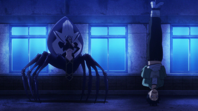 A man (Kurusu) is hung upside down in a dark room. A spider lady (Rachnera) looks at him from a short distance away.