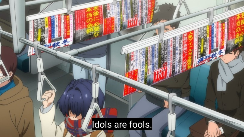 A girl stands in a crowded train. Subtitle: Idols are fools.