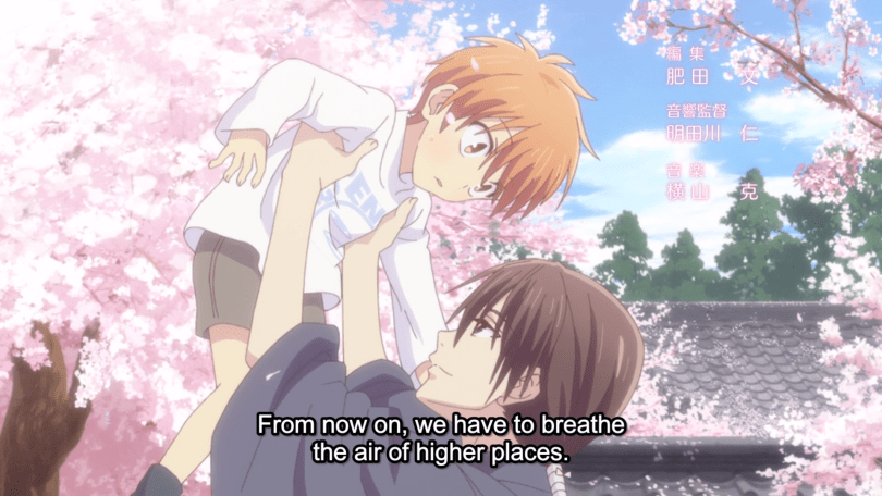 Kazuma lifts Kyo as a young child over hid head against a background of cherry blossom trees