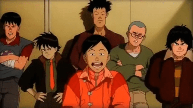Kaneda making an overly exagerrated well-behaved smile at the camera while his gang looks unimpressed behind him