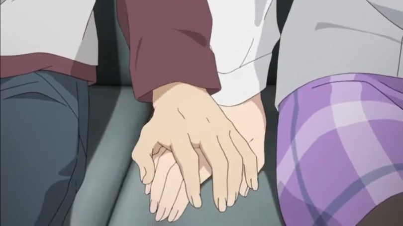 A close up of two people holding hands as they sit beside one another