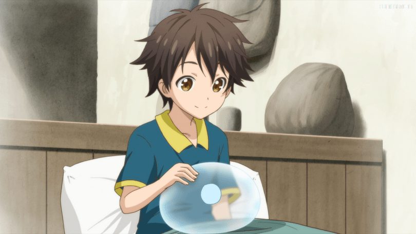 A boy holds a clear blue slime in his hands