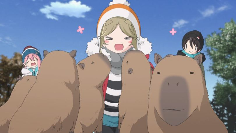 A delighted blonde girl in winter clothes surrounded by capybara